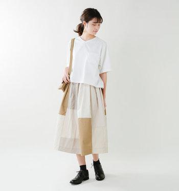 絶妙な丈感の白Tシャツは、タックインしなくても好バランスを作れるのが◎ 潔い無地の白Tシャツは、パッチワーク柄のデザインスカートを合わせてメリハリのある着こなしに。