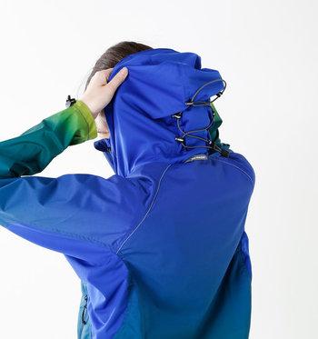 薄手のシャリ感のある撥水生地を使用。ややハリはありますが柔らかくて着心地はバツグンです。フードと袖口にはドローコードが付いていて冷たい風から首元や手首をしっかりガード◎。また、随所に反射パッチとリフレクターステッチが使われていて夜でも安全です!