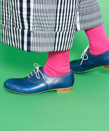 ブルーのシューズとパンツをつなぐのは、何とも鮮やかなショッキングピンクのソックス。シューズと対照的な色を配することで、一目置かれるモードな足元に。