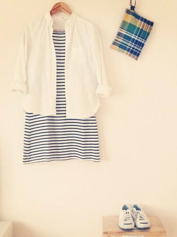 ボーダーのワンピースに、涼しげなマドラスチェックのクラッチバッグを合わせて。さらに真っ白なシャツを羽織り、好印象な清潔感をプラスします。