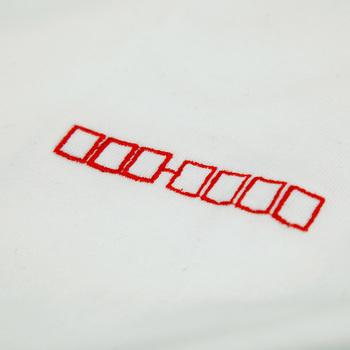 郵便番号欄をモチーフにした刺繍。ユーモアたっぷりなアイデアを効かせて。