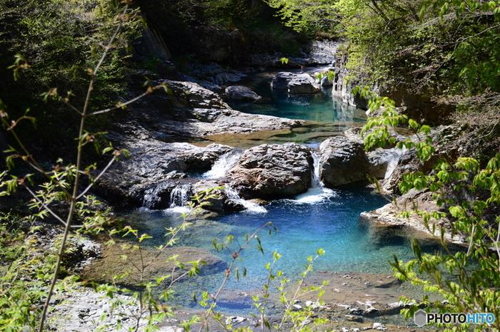 群馬県の天然記念物「四万の甌穴」でも、「四万ブルー」を見ることができます。甌穴は、数万年かけて水流と石などによってつくられた川底の穴で、四万の甌穴は3m以上もの深さのところもあるそうです。あたたかな季節は水遊びをしている人も見かけますよ。冷たい川の流れに足を入れると、気持ち良さそうですね。