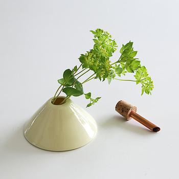つるんとした磁器のベースにコルク栓が差してあり、お水を入れる時には、このコルク栓をはずして行います。 コルク栓には銅管がついていて、ここに茎を差し込みお花を生けます。銅管がしっかりと茎を支えてくれるので、一輪のお花は勿論、細めの茎のお花でも、傾くことなく、きれいに生けることが出来ます。