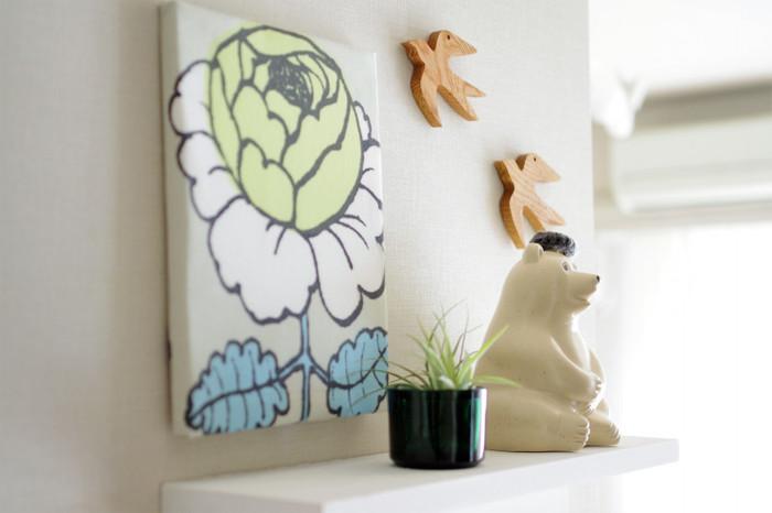 ファブリックパネルのすぐ下に飾り棚を配置して、北欧雑貨や観葉植物とのコラボレーションを楽しんでみてはいかがでしょう。オブジェをシックなものに変えればまた違った雰囲気に。お部屋の印象を少し変えたい時にぴったりです。