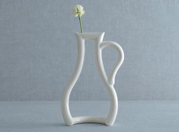 なんともユニークなこちらの花瓶は、徳田裕子さんデザイン、ceramic japan(セラミックジャパン)が作り上げる「still green」(未熟)というネーミングの一輪挿し。 リキュールを入れた小瓶がモチーフで、真っ白で柔らかな曲線を描く立体的なボディは、生けたお花をいっそう鮮やかに引き立ててくれます。