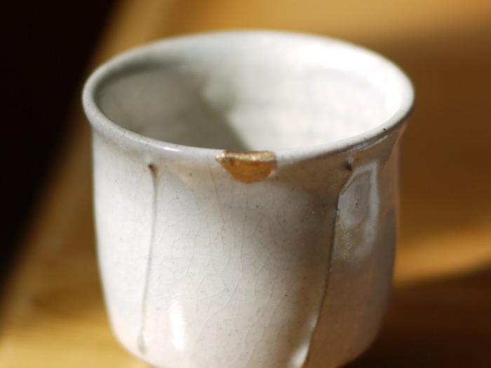 陶器の湯飲みの欠けに金継ぎがほどこされた物。最初からそういうアクセントを付けたデザインであるのかのようにしっくりとなじんでいます。