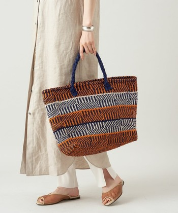 ナチュラルな風合いとエスニックなパターンが魅力のかごバッグ。ついついシンプルになりがちな夏のスタイリングに、大人っぽいアクセントを添えてくれます。A4がすっぽり入るサイズ感でデイリーに使いやすく、荷物の多い方でも安心!アフリカ・ケニアの女性たちの手でひとつひとつ丁寧に編まれたバッグは、丈夫で耐久性もあり長く大切に使えます。