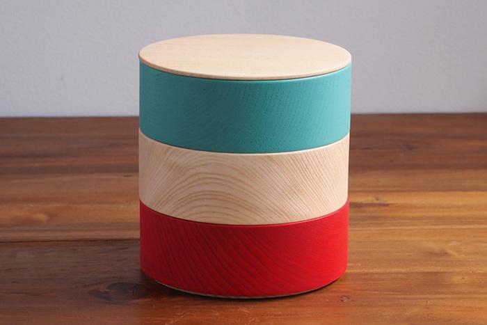 彩りが楽しい円筒形の重箱は、積み木やコマなど、懐かしい「木の玩具」をイメージして作られました。直径13.5cmの大きすぎないお重は、特別な日だけでなく、普段の食卓でも使ってみたくなります。