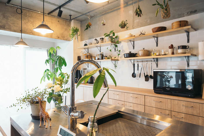オープンラックには、厳選されたキッチンツールがカテゴリーごとに並んでいます。バランス良く配置されたハンギングプランターや大きな観葉植物が、より居心地の良い空間に◎