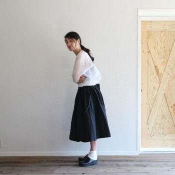 リラックス感あるビッグシルエットのヘンリーネックシャツをフワッと広がるミモレ丈のスカートと合わせて。靴下とサボまでホワイト×ブラック。細部まで配色のバランスが絶妙です。