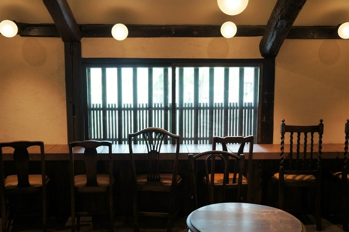 """店の1Fでは、地元名産の""""清水白桃""""を使ったプリンや羊羹などの土産類、テイクアウトのジェラートやジュースが販売されています。2Fは、落ち着いた雰囲気のカフェスペース。一人旅なら、倉敷川畔の風景を眺めながら頂ける、窓際のカウンター席がオススメ。"""