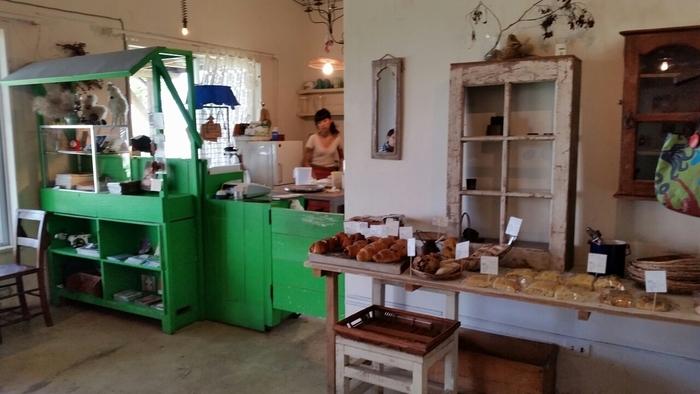 コンクリートの白い壁に、緑の棚が映える、かわいい店内。ちょっとカントリー調の雰囲気も漂います。流木や植物がセンスよく飾られていて、とても居心地がいいですよ。 そして、香ばしいパンの香りにワクワクするはず♪実は天然酵母を使った自家製パンが人気のお店で、パンの販売も行っています。