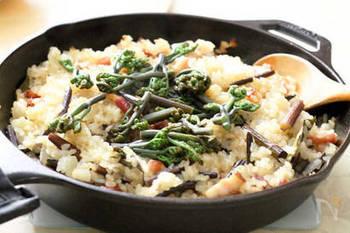 スキレットで作る、ちょっとオシャレなパエリヤレシピ。具材はベーコンとタマネギのみとシンプル。旬のわらびを洋風で楽しめます。