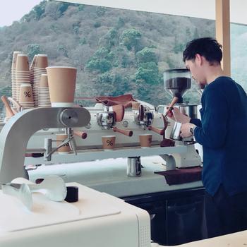 「%」のロゴと美しいラテアートがSNSでも人気の「アラビカコーヒー」。日本人実業家が手がけ、世界で展開するコーヒーショップで、国内では京都に3つの店舗があります。中でも「アラビカ京都 嵐山」は、桂川の流れに面し、真向かいに嵐山の景観が広がる絶好のロケーション。せせらぎとそよ風を浴びながら、こだわりの一杯を味わえます。