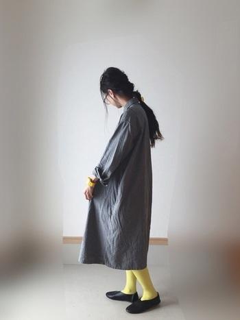 モノトーンのシンプルワンピには、ちょっとハードル高めの発色のいい黄色のカラータイツや腕時計を合わせて。グレー×イエローは、思いのほか相性抜群の色コンビであることに気付くはず。
