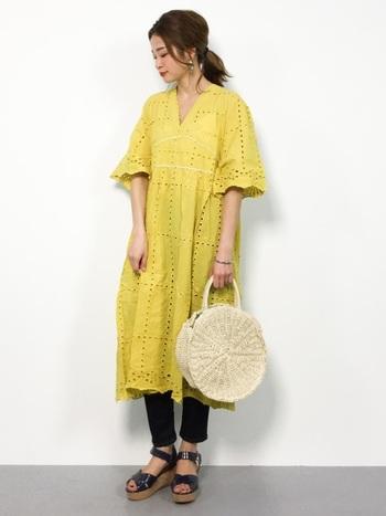 黄色のワンピースには、黒のスキニーとサンダルを合わせてワンピの存在感を引き立たせましょう。かごバッグで季節感もプラス。