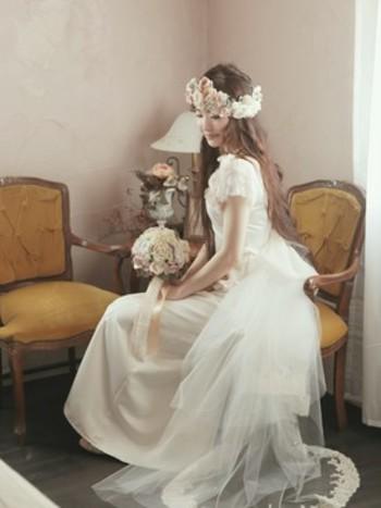 チュールが段になったロマンティックなデザインのドレスには、そんな雰囲気にぴったりの花冠とブーケで。ダウンスタイルの髪型もより世界観を深めます。