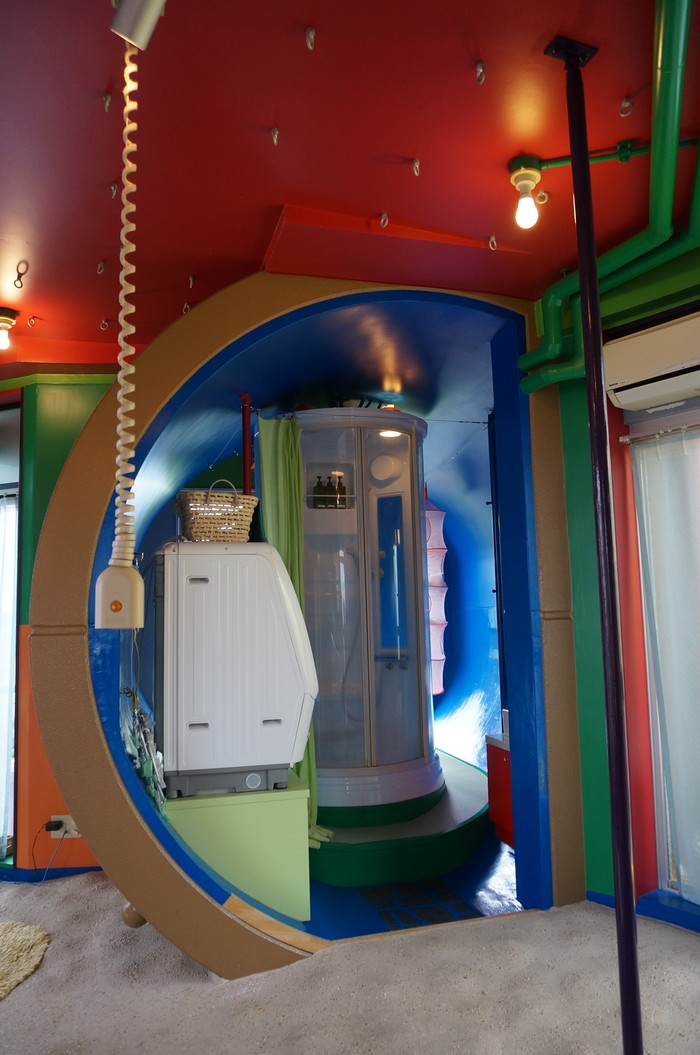 「bath room」は円筒状の空間です。真ん中がシャワールームで、左にドラム式洗濯機、右に洗面所があります。そして、シャワーの後ろに回ると…