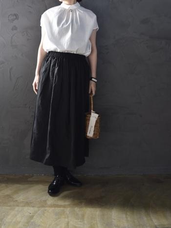 白のブラウスに、黒のロングスカートを合わせた着こなし。トップスは袖が短めになっているので、夏らしい爽やかなモノトーンコーデにもぴったりです。スカートから足元まで黒でまとめて、白ブラウスの清楚感を強調しています。