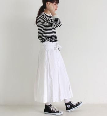 白のロングスカートに、ボーダートップスとスニーカーを合わせたスタイリング。モノトーンコーデに柄をプラスするだけで、無地の白黒コーデよりも軽やかさがアップします。
