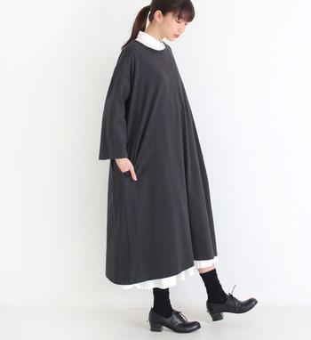 ゆったりシルエットの黒ワンピースに、白のシャツワンピースをレイヤードしたスタイリング。襟元と裾からちらりと見える白が、シンプルな黒ワンピースに華やかさをプラスしています。