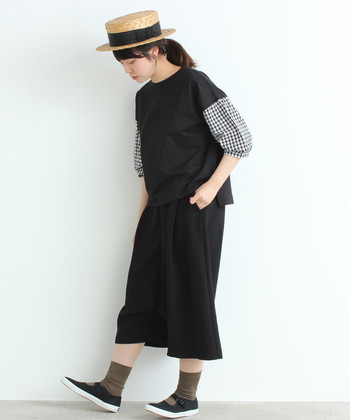 袖にモノトーンのチェック柄があしらわれた黒トップスに、黒のスカートを合わせたスタイリング。白の靴下を合わせても素敵ですが、モノトーンコーデにはアースカラーもよく馴染みますね。