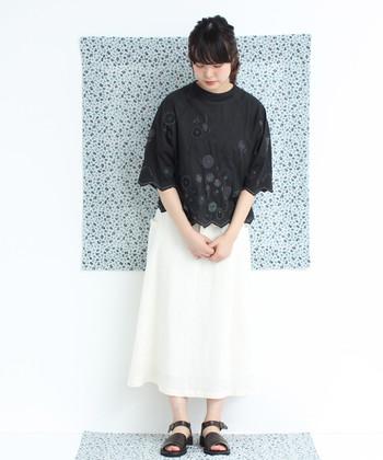 北欧風のフラワー刺繍が施された黒トップスに、白のロングスカートを合わせた爽やかなモノトーンコーデ。真っ黒なトップスを選ぶよりも、さりげなくデザインが入っているアイテムを選ぶと、季節感のある爽やかさを演出できます。