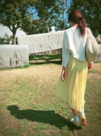 白いトップスに黄色のプリーツスカートで軽やかに。足元も黄色で揃えて全体的に統一感を。