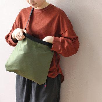 """エンジ色のトップスにオリーブのバッグを合わせた、ナチュラルなアースカラーコーディネート。バッグとウェアを同系色でまとめると""""こなれ感""""のあるオシャレな着こなしになります。"""