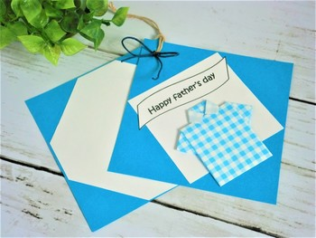 """ファッション好きな""""おしゃれパパ""""なら爽やかなチェックシャツの折り紙を貼りつけた手作りカードがおすすめ。  折り紙でシャツを貼り、メッセージシールなどでデコレート。土台のスクエアカードを二枚つづって完成です。"""