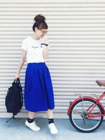 目が覚めるような鮮やかな青のスカートには、美シンプルなロゴTがベストマッチ。小物は黒で揃えて、足元はTシャツの白とリンクさせたさりげない統一感がおしゃれです。