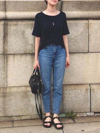 程よくゆったり感のある黒Tシャツとスタンダードなデニムを合わせたスタイル。広めの首元の開きが女性らしい印象です。黒のスポーツサンダルと合わせて程よく軽さと抜け感を加え、初夏らしい着こなしに。