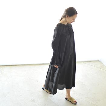 漆黒のワンピースをまとい、ローテンションなフォークロアルックを堪能。サンダルはベージュのクロスデザインを選び、ブラックが持つ重たさを開放します。
