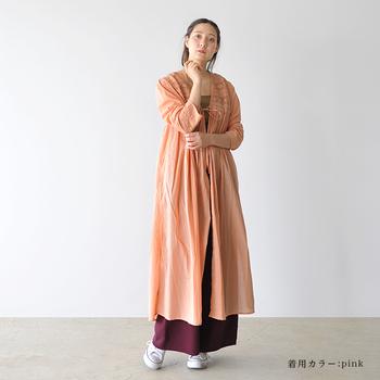 ピンクの前開きワンピースに、ワインレッドのロングスカート。女性らしい色を重ねることで、トライバルスタイルにさり気ない艶やかさが備わります。