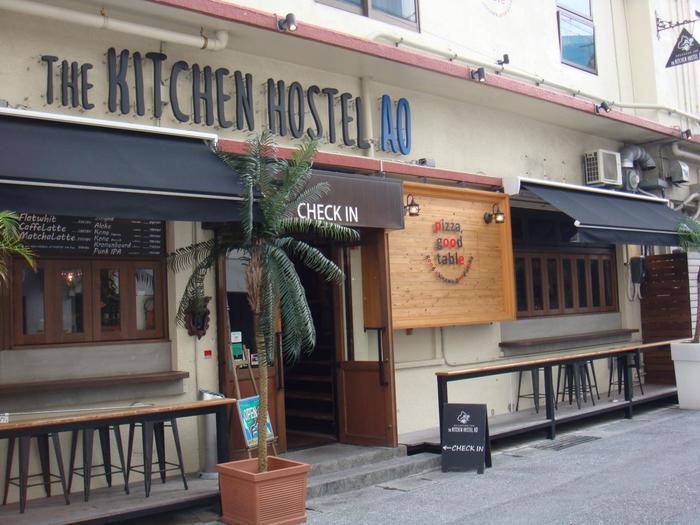 """沖縄に着いて、那覇で過ごすなら「The Kitchen Hostel AO」がおすすめです。国際通りの近くにあり利便性が抜群ですし、おしゃれなインテリアは""""旅""""気分を演出してくれます。1階の「pizza, good table」のカウンターでチェックインして、2階へ。"""