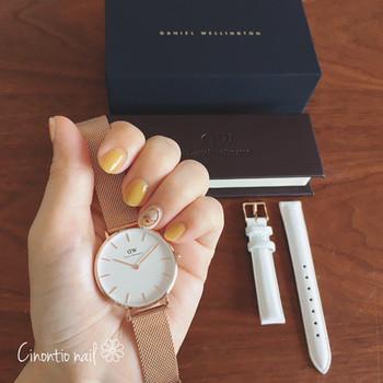 クラッシーなゴールドの腕時計を、チアフルイエローのネイルがカジュアルダウン。ネイルの色を明るくすることで、ゴールドの光沢がさり気ない輝きに変わります。