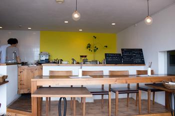 黄色×白の壁面に、小さめのペンダントライト、シンプルな木製家具…。センスの良さを感じさせる、心地よい空間です。