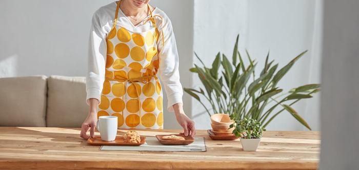 色合いの微妙に異なるイエローのドットが大胆なエプロンは、ドレスのような存在感。あわただしい朝食づくりも、疲れて帰ってきたときの夕食づくりも、やる気にしてくれるはず。