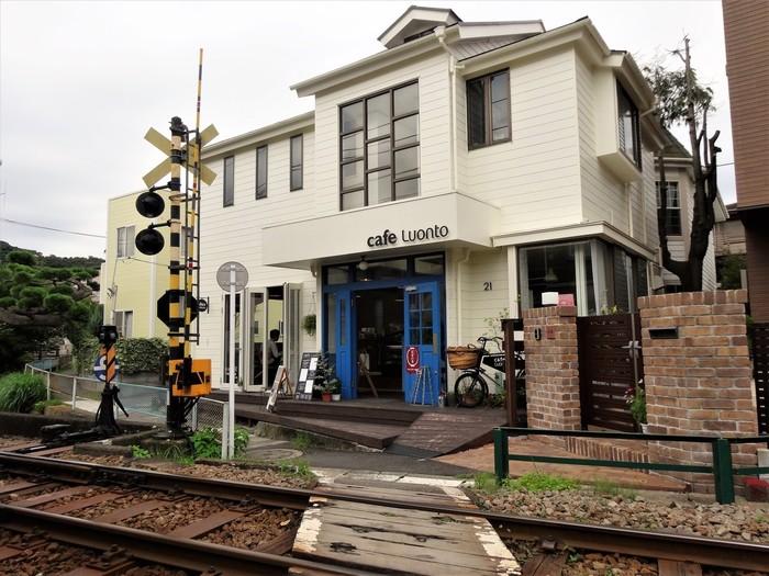 真っ白な壁に青い扉が可愛らしいのは「Cafe Luonto(カフェ ルオント)」です。長谷駅を出て由比ヶ浜方面へ。路地裏探検のような気分で、川沿いの細い道を進んでいくと…発見!江ノ電の線路わきにありますよ。