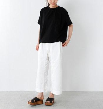 夏らしい白ボトムスとの組み合わせ。ゆるっとした黒Tシャツにくるぶし丈の白のワイドパンツで、大人リラックス感を作っています。ウッドソールのサンダルもマッチしています。