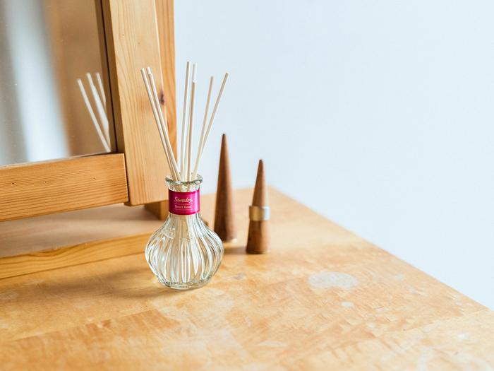 花の蕾のような形状をしたガラス瓶が可憐な佇まいの『日比谷花壇セレクト』シリーズ。ご存知の、全国的に知られている花屋「日比谷花壇」が香りのオイルを選び作られたシリーズです。  ピンクのラベルが可愛らしい「スウィートローズ」はネーミングの通り、ローズを中心に作られたフローラルブーケの香り。女性らしい香りが広がるのでドレッサー付近に置いてみると、おしゃれの気分も高まりそうです。