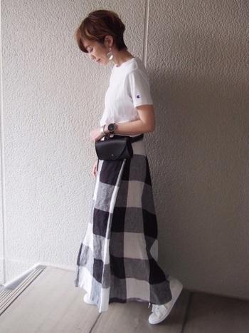 大きめブロックチェックのスカート×Tシャツに白のスニーカーを合わせたシンプルコーデ。革のウエストポーチで上質感をプラスして。