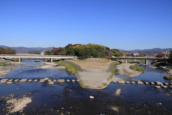 """【画像は、賀茂大橋から望む賀茂川と高野川が合流する三角地。その北に広がる森は「下鴨神社」の境内の一部""""糺の森""""です。高野川(画像左)に架かるのが、「出町柳駅」前から続く""""河合橋""""、鴨川(画像中央から右)へ架かるのが""""出町橋""""。】"""