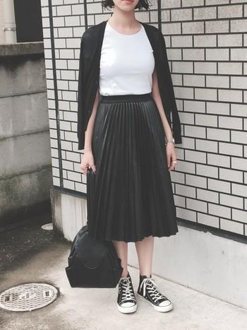 タイトな白Tシャツにプリーツスカート、黒のカーディガンを肩掛けしたスカートスタイル。質感や色の割合で、重たくなりがちなモノトーンコーデをすっきりと見せています。