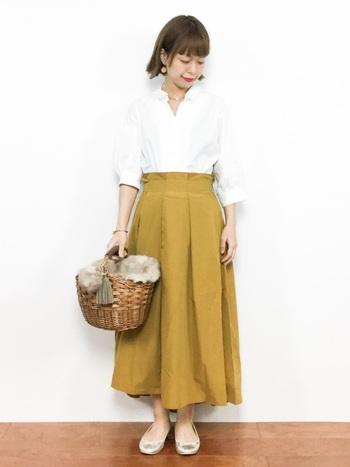 落ち着きのあるマスタードイエローのロングスカートと爽やかな白のスキッパーシャツの組み合わせ。トップスをインしてきちんと感を楽しみつつ、足元はメタリック系カラーのバレエシューズで軽やかな遊び心を添えています。