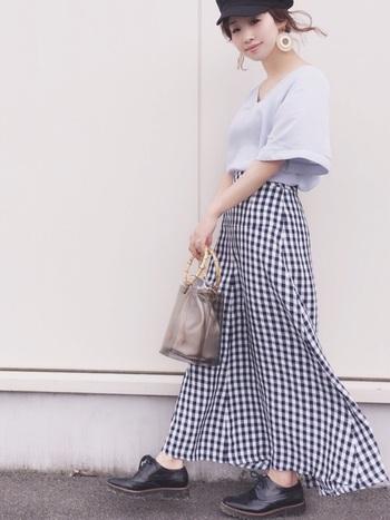 ふんわり女性らしさが引き立つトップスとロングスカートに、マニッシュなシューズを合わせた着こなし。ビニールバッグのバンブーハンドルと、スカートのチェック柄がナチュラル感を高めています。