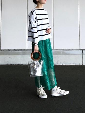 モノトーンのボーダートップスに、鮮やかなグリーンのスカートを合わせたコーディネート。インパクトあるスカートにも負けない、エッジの効いたビニールバッグがさらなるセンスアップを底上げしています。