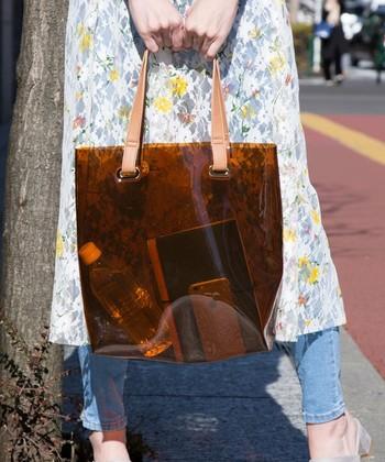 """荷物がたくさん入る「トートバッグ」もビニール素材で取り入れれば、いつもとは違った印象に。中の荷物が透けて見えるほどよい""""緊張感""""が新鮮!無駄のない私生活まで、着こなしとして楽しめるアイテムです。"""