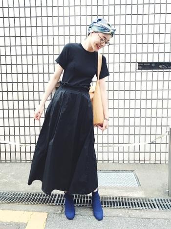 黒のロングフレアスカートと合わせれば、一体感が生まれワンピースのように見えます。青のショートブーツと頭に巻いたスカーフで小物のカラーをリンクさせ、シックな装いに程よいアクセントをプラス。