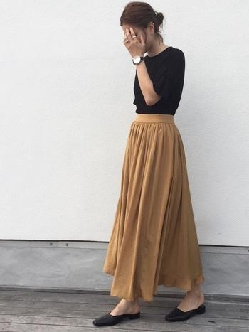 ジャストサイズの黒Tシャツと柔らか素材のベージュのロングスカートの組み合わせ。フェミニンなボトムスもトップスや小物を黒で引き締めることで、シックな大人のスタイリングに仕上がります。